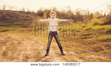 cute little girl standing with hands to sides on a road in countryside