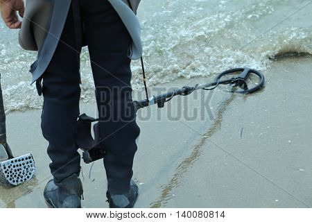 Man With Metal Detector On The Beach To Find Lost Objects