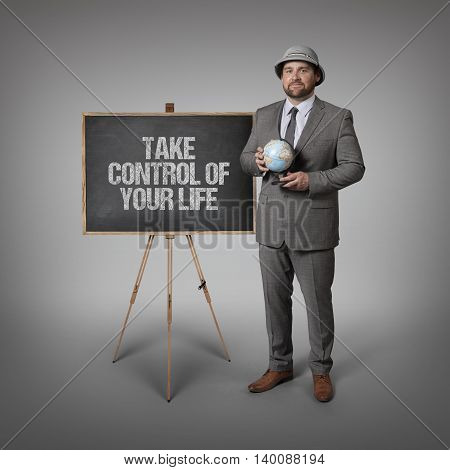 Take control of your life text on blackboard with businessman holding globe in hands
