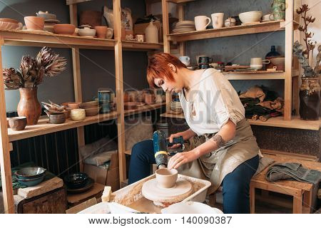 Pottery drying with special dryer. Carefully working young female potter. Small business of woman