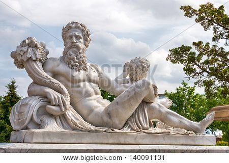 Marble statue of Greek Olympic god with cornucopia in his hands