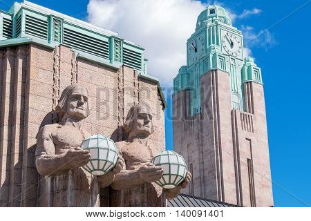 Granite statues holding lamps and Clock tower at the Central Railway Station. Helsinki Finland Europe