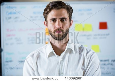 Portrait of confident businessman standing against whiteboard in meteing room
