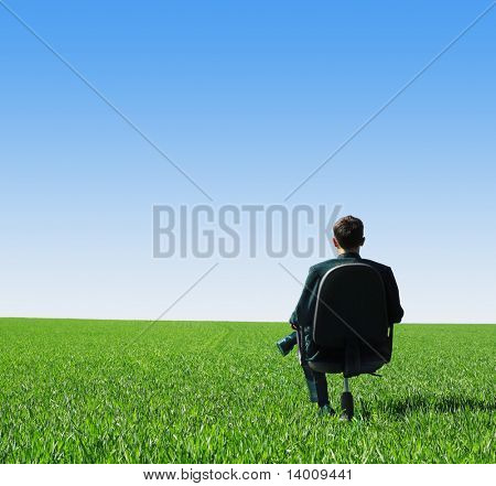 Man in suit sitting on chair in green field