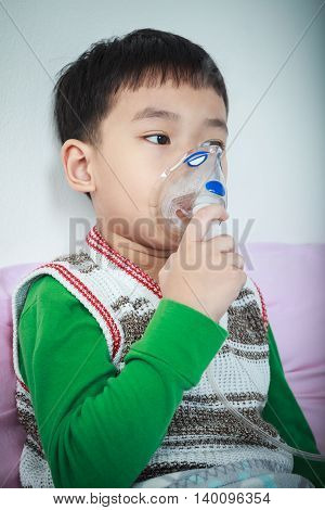 Sad asian child holds a mask vapor inhaler for treatment of asthma on sickbed in hospital. Breathing through a steam nebulizer. Concept of inhalation therapy apparatus. Vignette style.