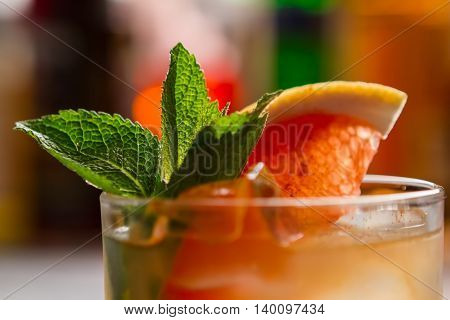 Cocktail with slice of grapefruit. Green leaves of mint. Exotic drink named Cobas. Chilled whiskey and fresh juice.