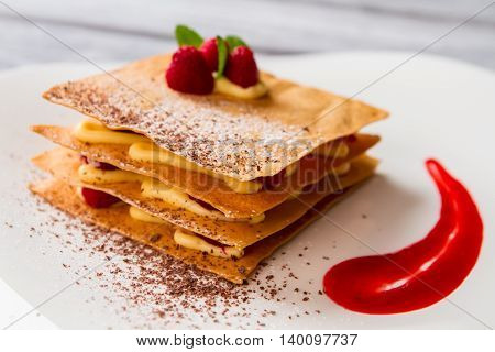 Dessert with chocolate crumbs. Red sauce and custard. Raspberry millefeuille ordered in cafe. Best recipe of french pastry.