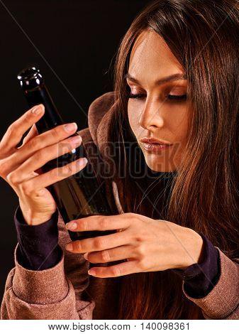 Drunk girl holding bottle of alcohol. Soccial issue alcoholism. Alcohol bottle in hands of drunk girl.