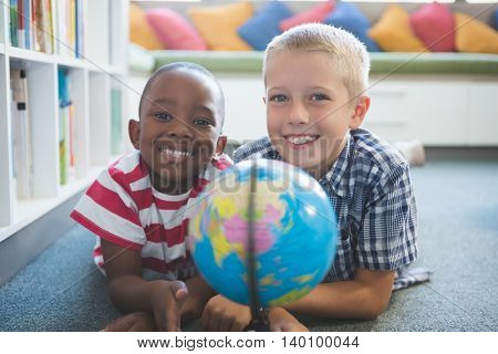 Portrait of school kids lying on floor studying globe in library at school