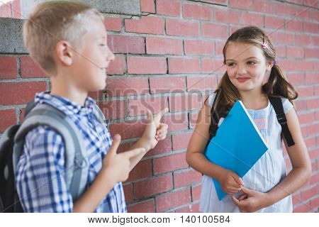 Smiling schoolkids standing in corridor and talking to each other at school