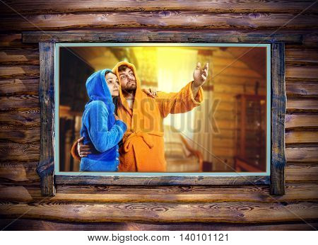 Woman in blue pijamas and man in yellow bathrobe looking out the window