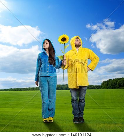 Woman in blue pijamas and man in yellow bathrobe holding sunflower on the meadow