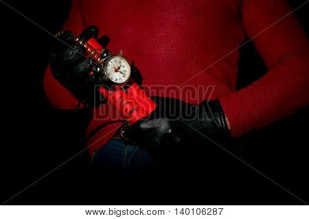 Terrorist in red sweater and gloves holds in hands time bomb
