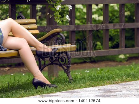 female legs in black sandals in the summer, on the bench, next to a fence with flowers, a woman short dress, legs crossed, blue dress and brown with yellow bench with armrests carved