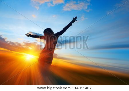 Young woman on meadow under sunset light with abstract motion