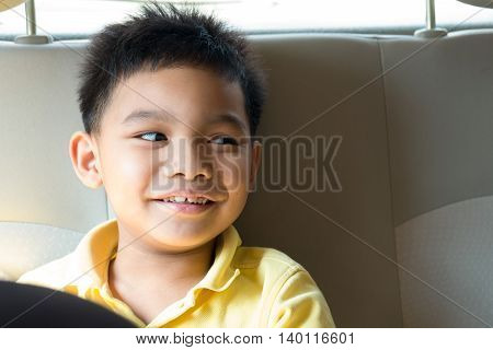 Asian seven years old boy smiling on back seat of car he is wearing a yellow shirt and looking for something.