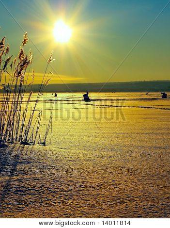 Winter fishermens on ice under sun