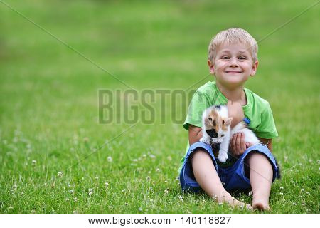 boy playing with motley cat on green grass