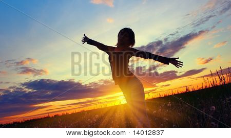 Young woman's silhouette over sunset light