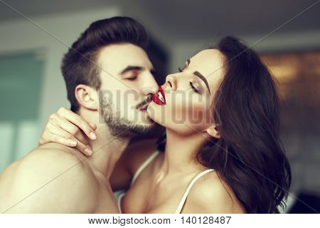 Sexy passionate couple foreplay at home red lips closed eyes