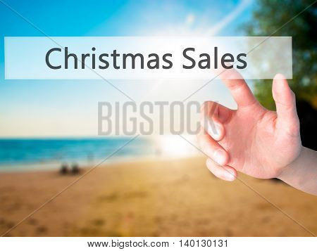 Christmas Sales - Hand Pressing A Button On Blurred Background Concept On Visual Screen.