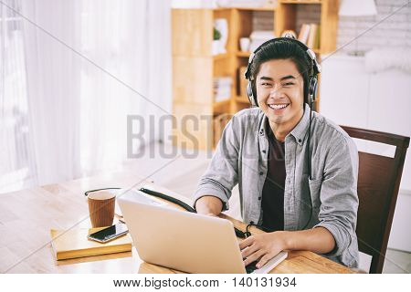 Asian student in headphones working on laptop at home