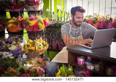 Male florist using laptop at his flower shop