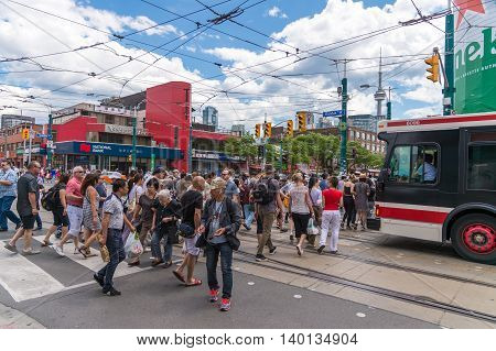 Dundas and Spadina corner in Toronto with people walking in the crosswalk and CN tower in the background