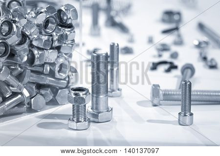 blue toned industrial nuts and bolts close-up