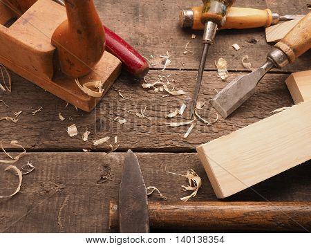 Old carpenter tools on a wooden workbench poster