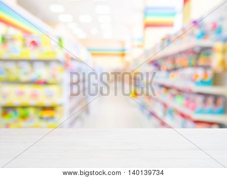 White wooden board empty table in front of blurred background. Perspective white wood over blur in kids toys store - can be used for display or montage your products. Mockup for display of product.