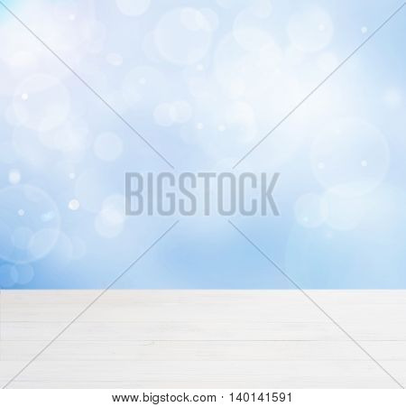 White wooden board empty table in abstract blue background with bokeh. Perspective white wood board over blurred blue background - mockup for display of product