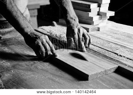 hands of the craftsman cut a piece of wood poster