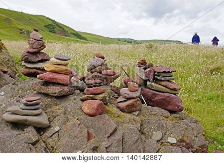 Foreground stacks of stones, or cairns, mark the way along a hiking trail in Scotland, with two hikers passing in the distance. Selective focus on cairns.