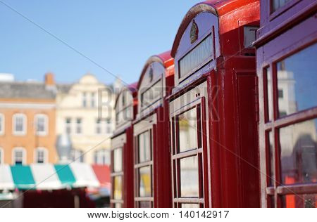 CAMBRIDGE, UK - AUGUST 22: Four red British telephone boxes sit in a row near the city centre market square in Cambridge, England on August 22, 2015.
