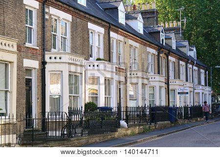 CAMBRIDGE, UK - SEPTEMBER 6: A man walks along a street of terraced houses in Cambridge, England on September 6, 2016.