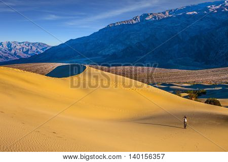 Bright sunny morning in a picturesque part of Death Valley, USA. Mesquite Flat Sand Dunes. Woman in striped shirt and straw hat  photographing sand waves