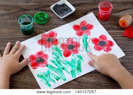 Drawing On Paper Poppies, Child Draws Fingers Grass. Glue, Paint, Paper And Potatoes On A Wooden Tab