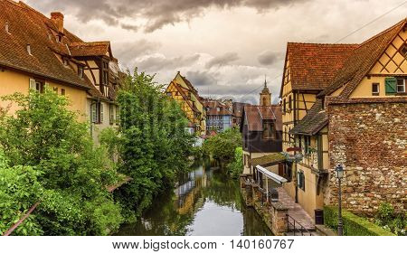 Famous traditional colorful timbered houses in Little Venice, petite Venise and tower of the church, Colmar, Alsace, France
