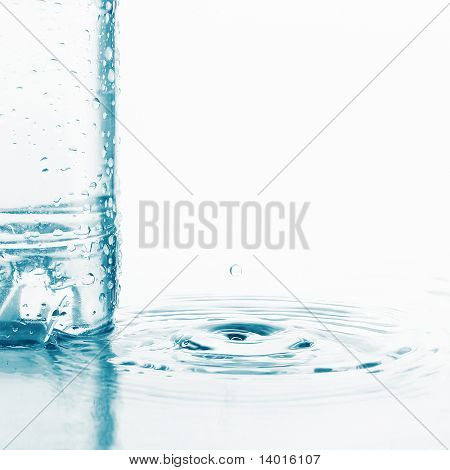 Plastic wet bottle with water and little drop with ripples on water surface