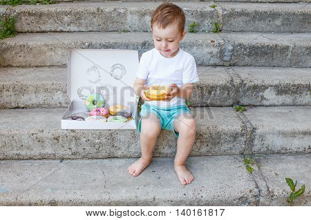boy licking lips looking at donut. child sitting on the stairs with a box of donuts and licks his lips in anticipation