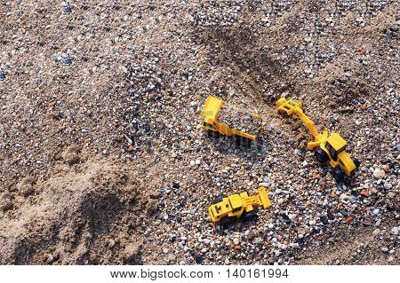 stone mining. toy excavator, truck and loader in a quarry. top view.  empty space for your text