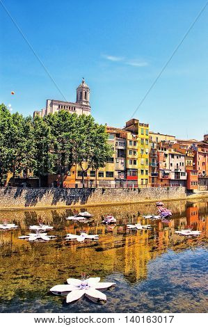 GIRONA, SPAIN - MAY 10, 2015: Flowers and house's reflection in Onyar River during Festival of floral decorations in Girona Catalonia Spain