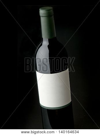 Wine bottle shot against black background with blank label