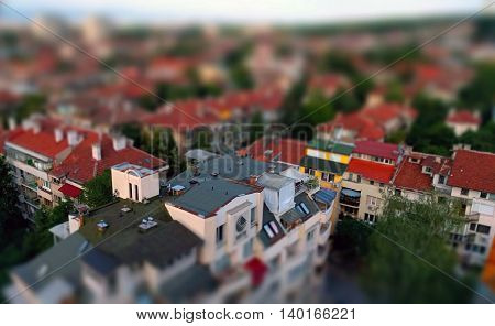 Small toy like miniature tilt-shift effect photo of a residential housing top roof terraces and trees in-between the buildings