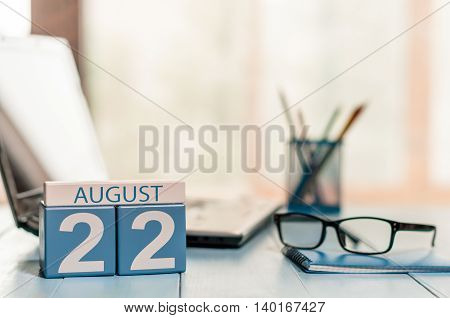August 22nd. Day 22 of month, wooden color calendar on HR office background. Summer time. Empty space for text.