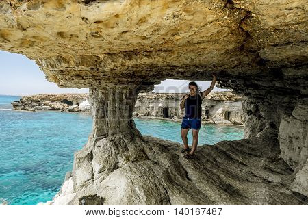 Girl posing in a rocky arch at Cape Greco. Cyprus