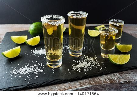 Tequila shots with lime on black stone background. Strong alcohol drink. Gold Mexican tequila shots.