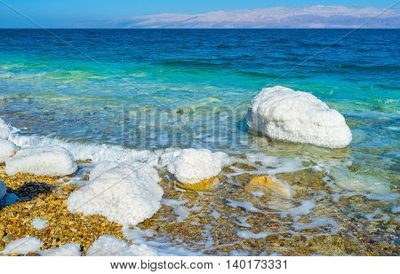 The calm shore of the Dead Sea with the white stones covered with salt Ein Gedi Israel.