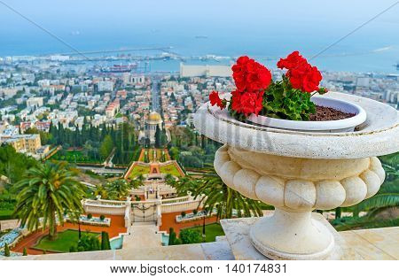 The stone vase with the bright red flowers decorates the handrail at the Bahai Garden viewpoint on the Carmel Mount top Haifa Israel.